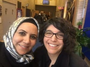 A Muslim woman in a head scarf and a Jewish woman stand together smiling