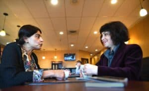 Two women face each other across a table talking with mugs of coffee