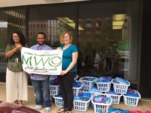 People holding a banner that reads MWC in front of baskets of Ramadan donations