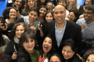 Women posing for a photo with Senator Cory Booker