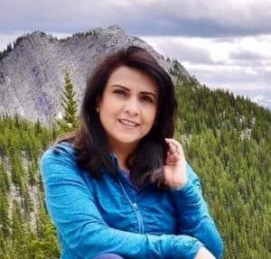 Photo of woman in blue jacket standing before mountains and green forest