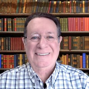 photo of dark haired man in glasses and plaid collared shirt standing before a wall of books