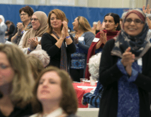 Women standing and clapping