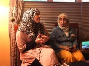 Two Muslim women talking in chairs
