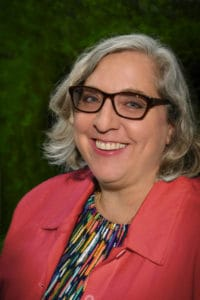 headshot of smiling woman in glasses and red blazer