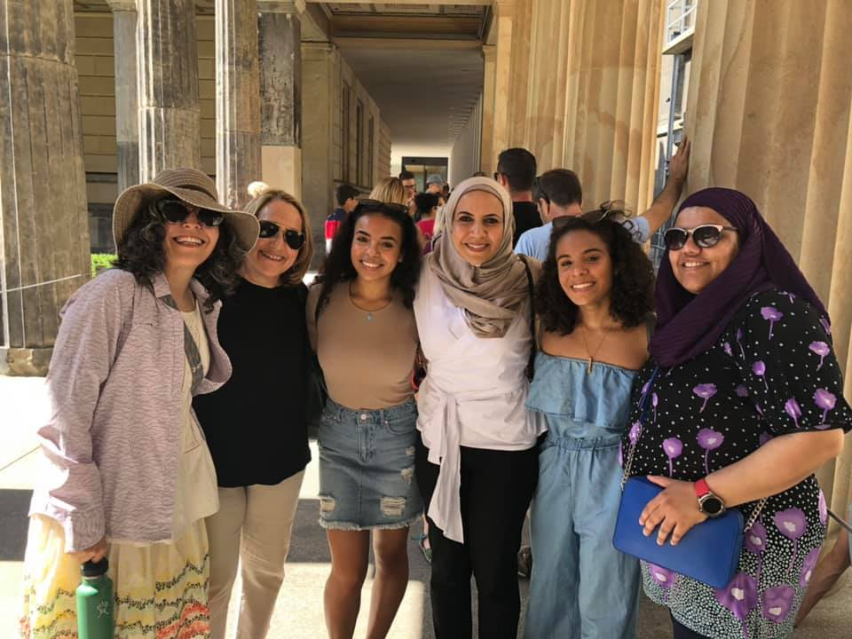 Smiling women in headscarves and hats posed between columns