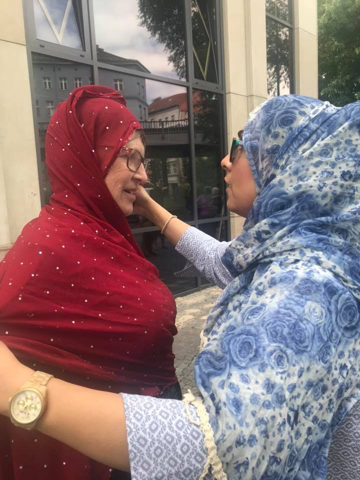 Woman in Red headscarf embracing woman in blue headscarf