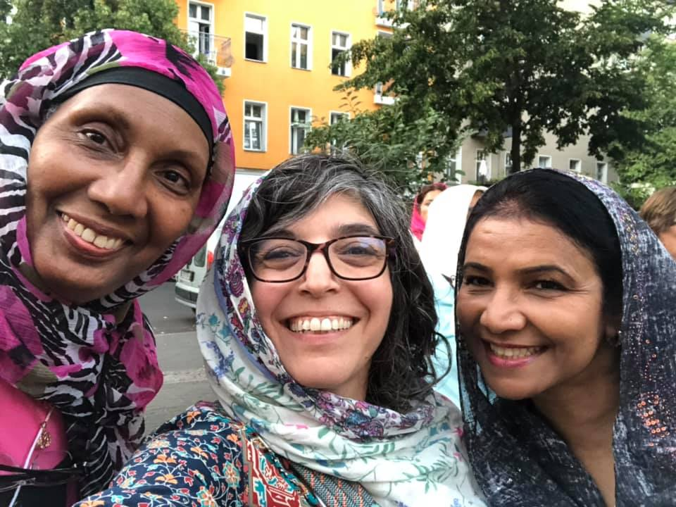 Three smiling women in headscarves