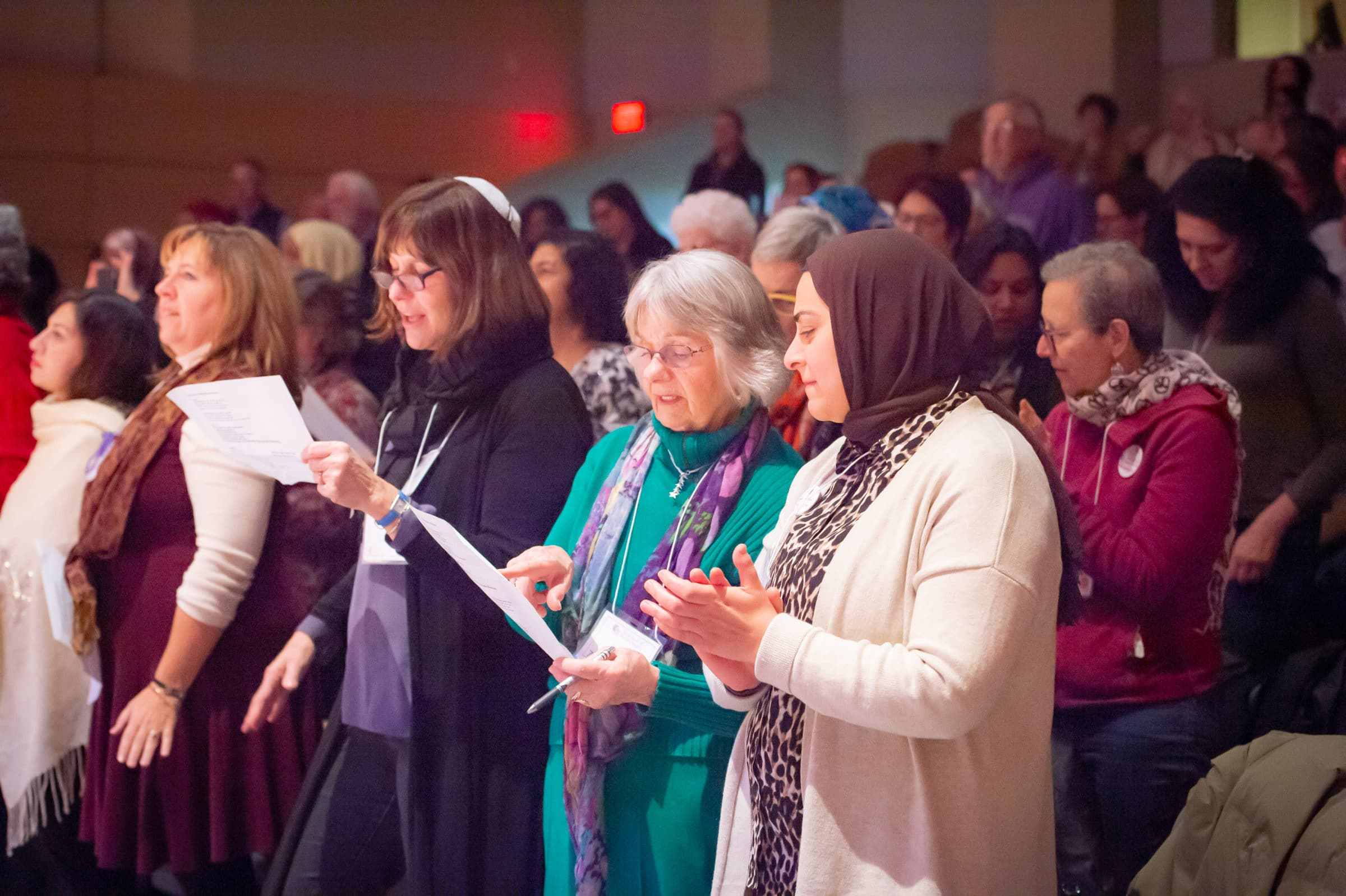 women standing and sharing a song sheet