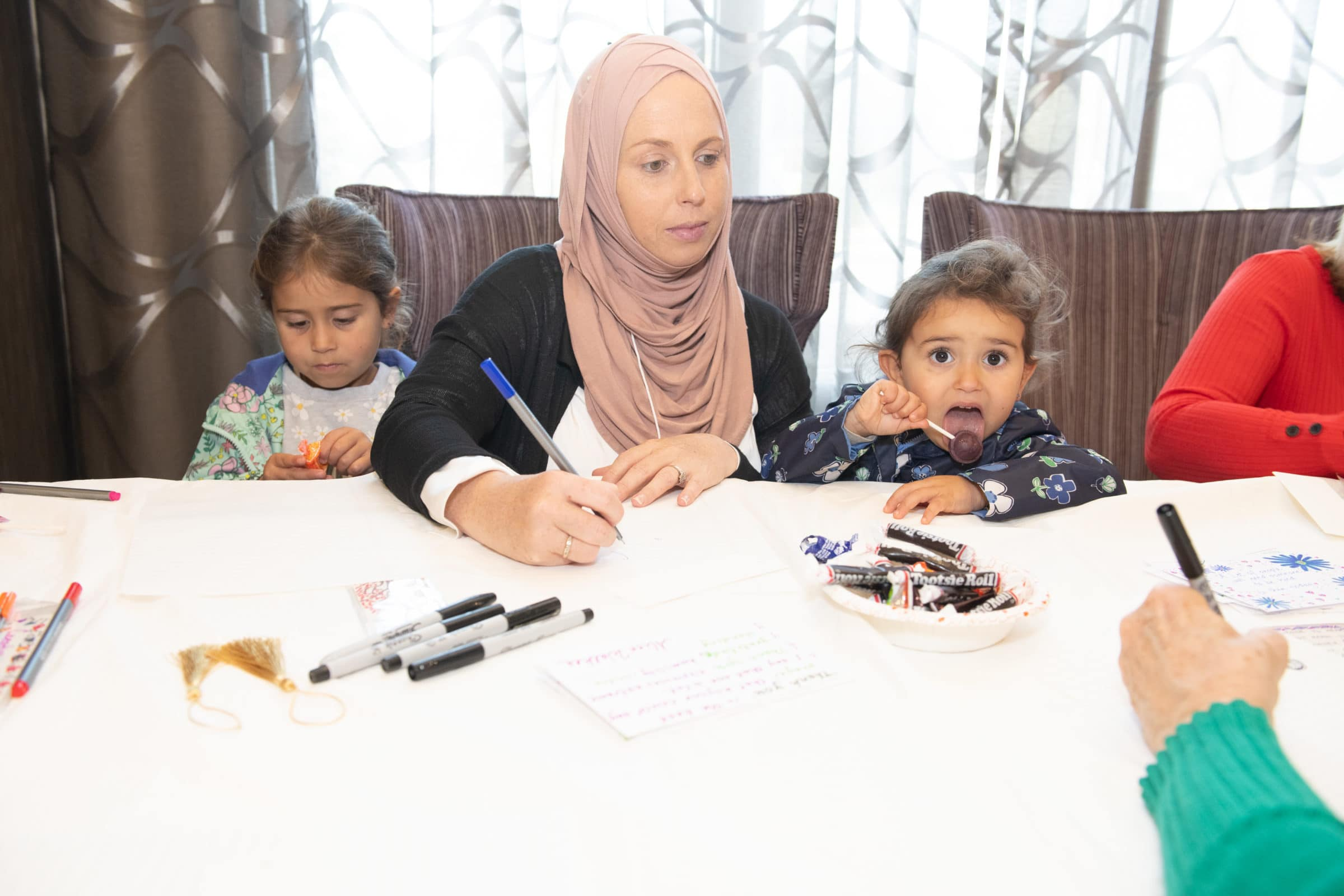 woman in hijab seated between two young girls