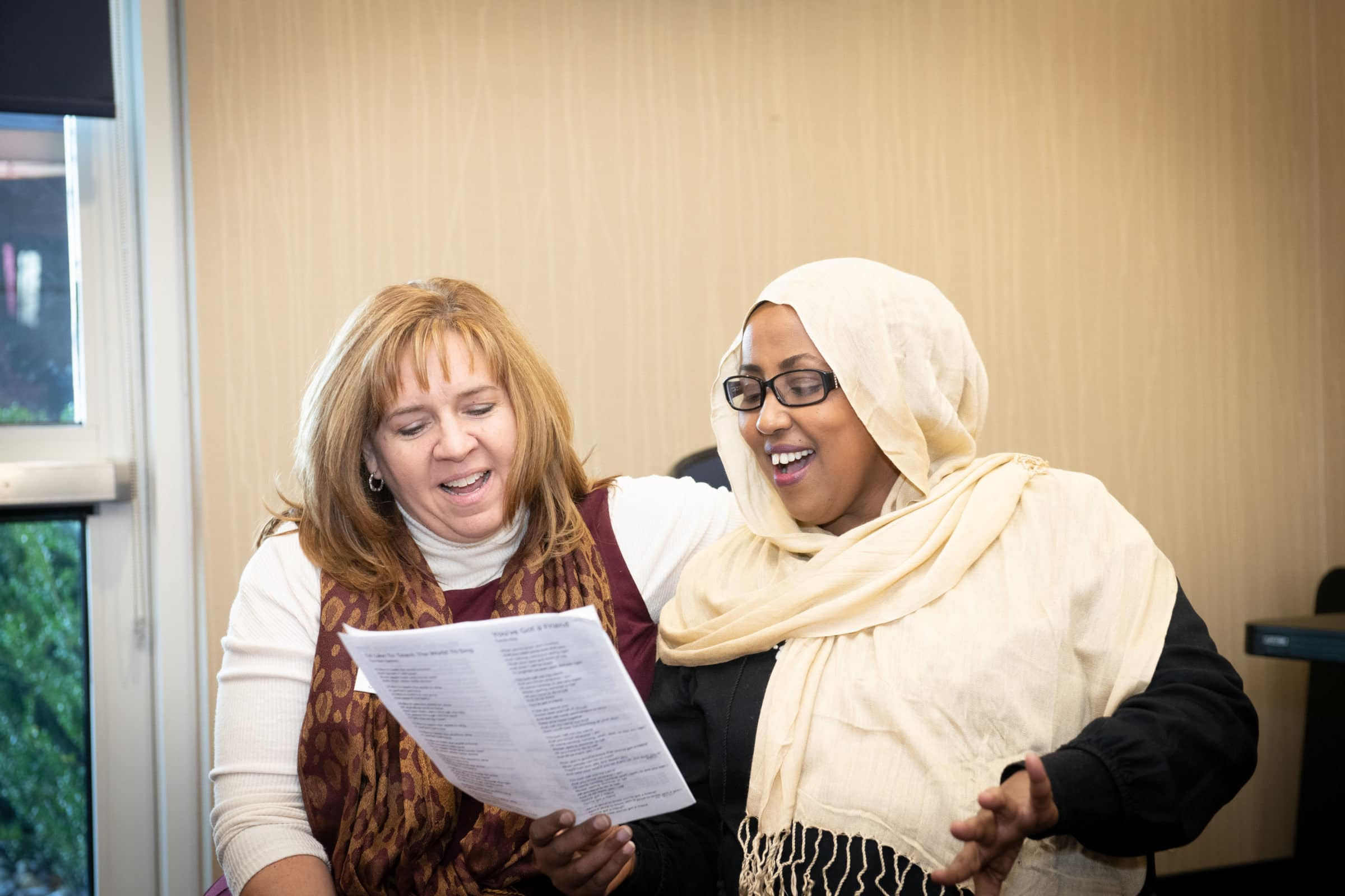 two women, one in hijab, sharing a song sheet