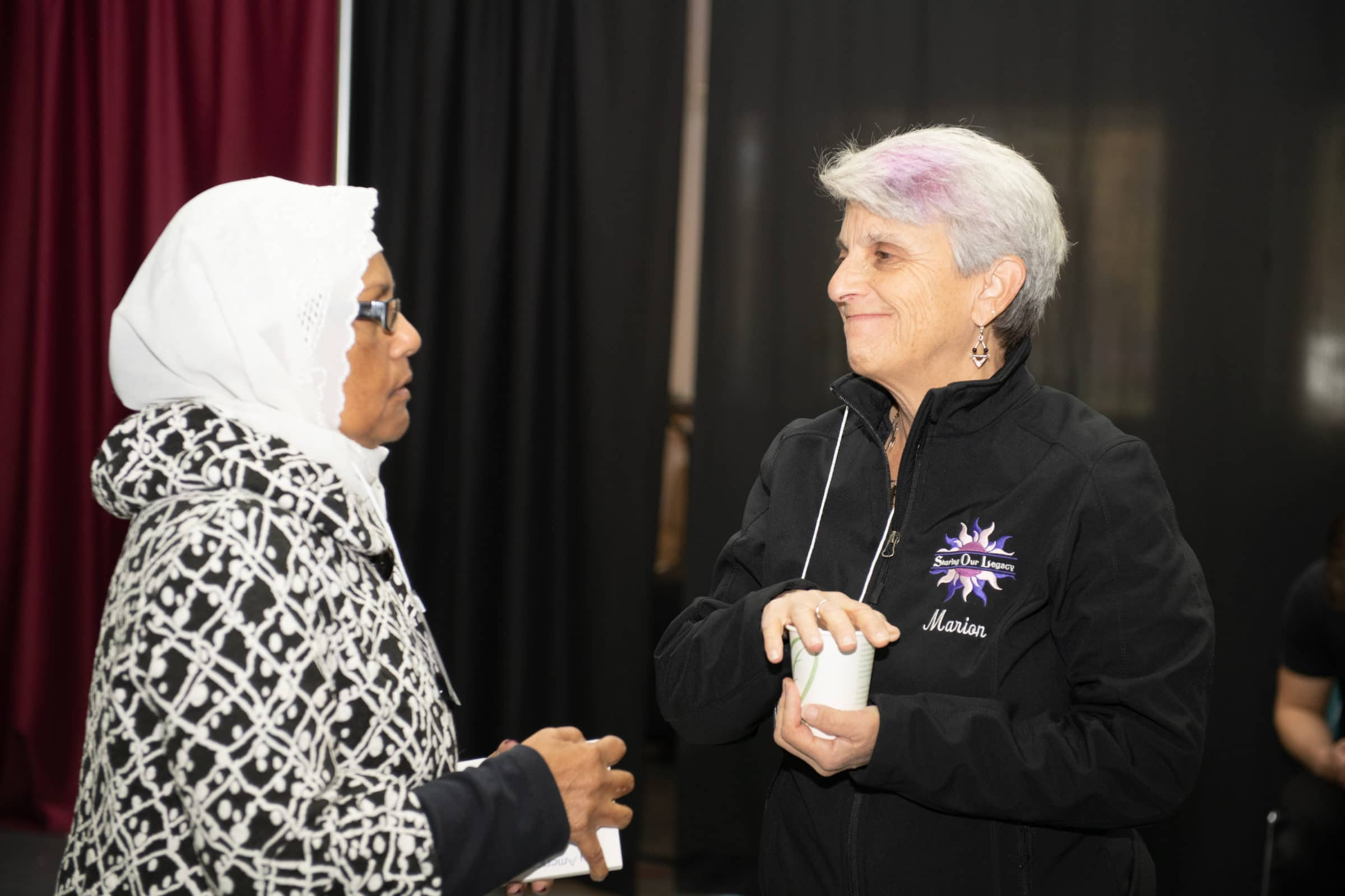 woman in hijab speaking to woman with purple streak in hair