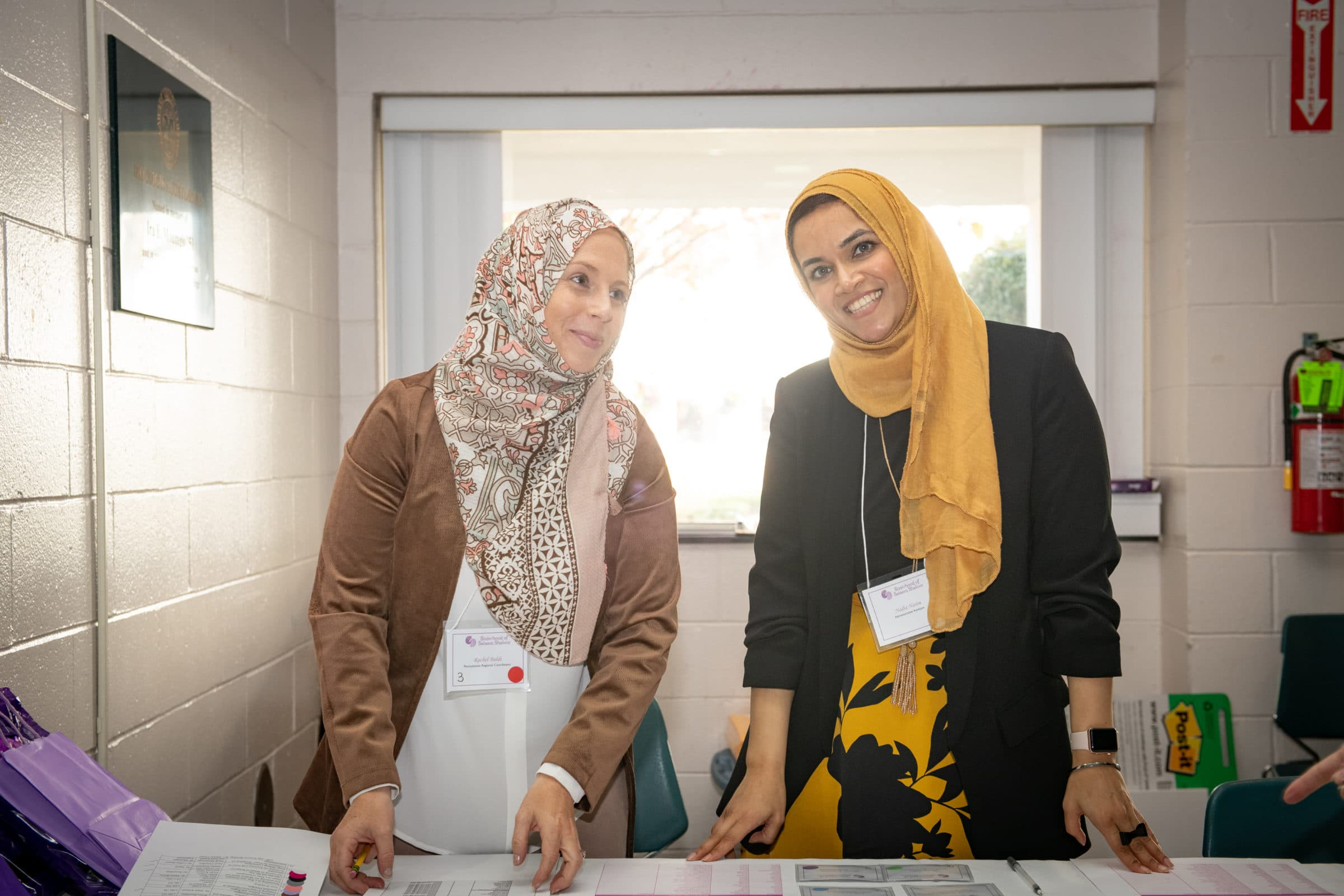two women in hijab standing at table in smiling