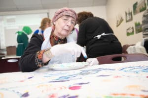 woman in headscarf working on an art project