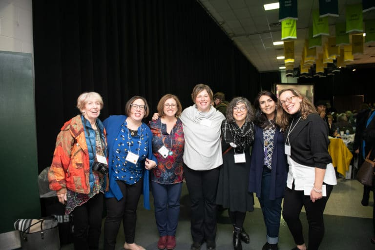 Group of women wearing conference badges pose for a photo, arms around each other