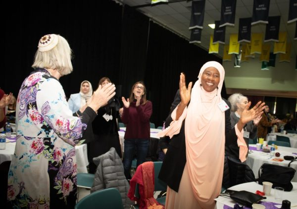 Muslim woman in hijab clapping, surrounded by other clapping women