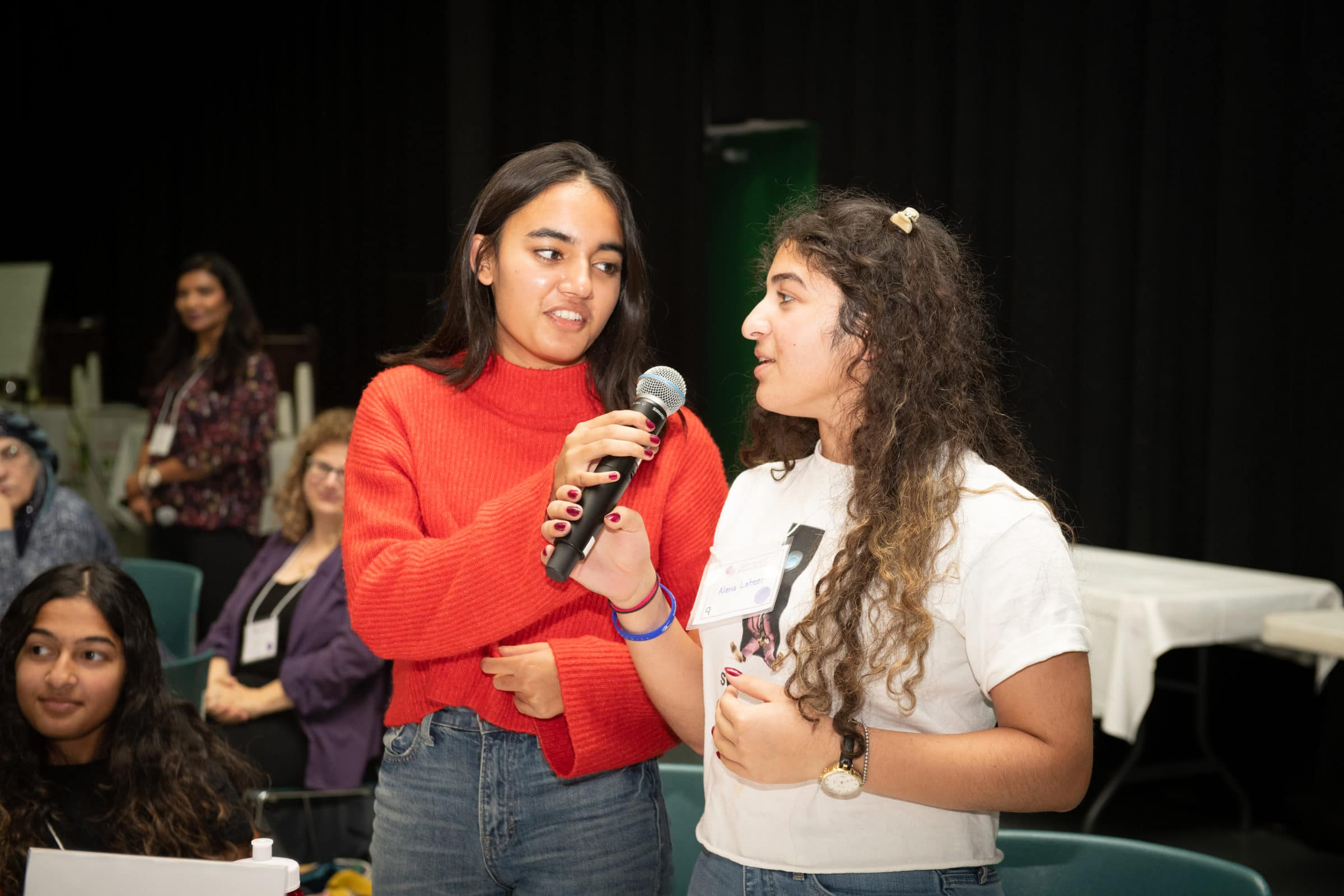 teen in orange sweater holding microphone for second teen in white t-shirt