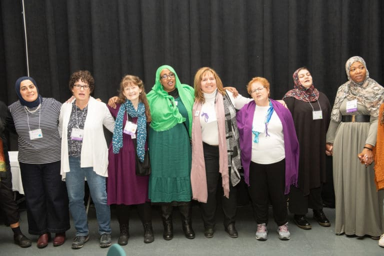 Muslim and Jewish women standing before a black curtain, their arms around one another