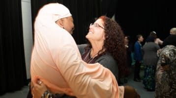 Muslim woman in hijab hugs woman with curly hair and glasses