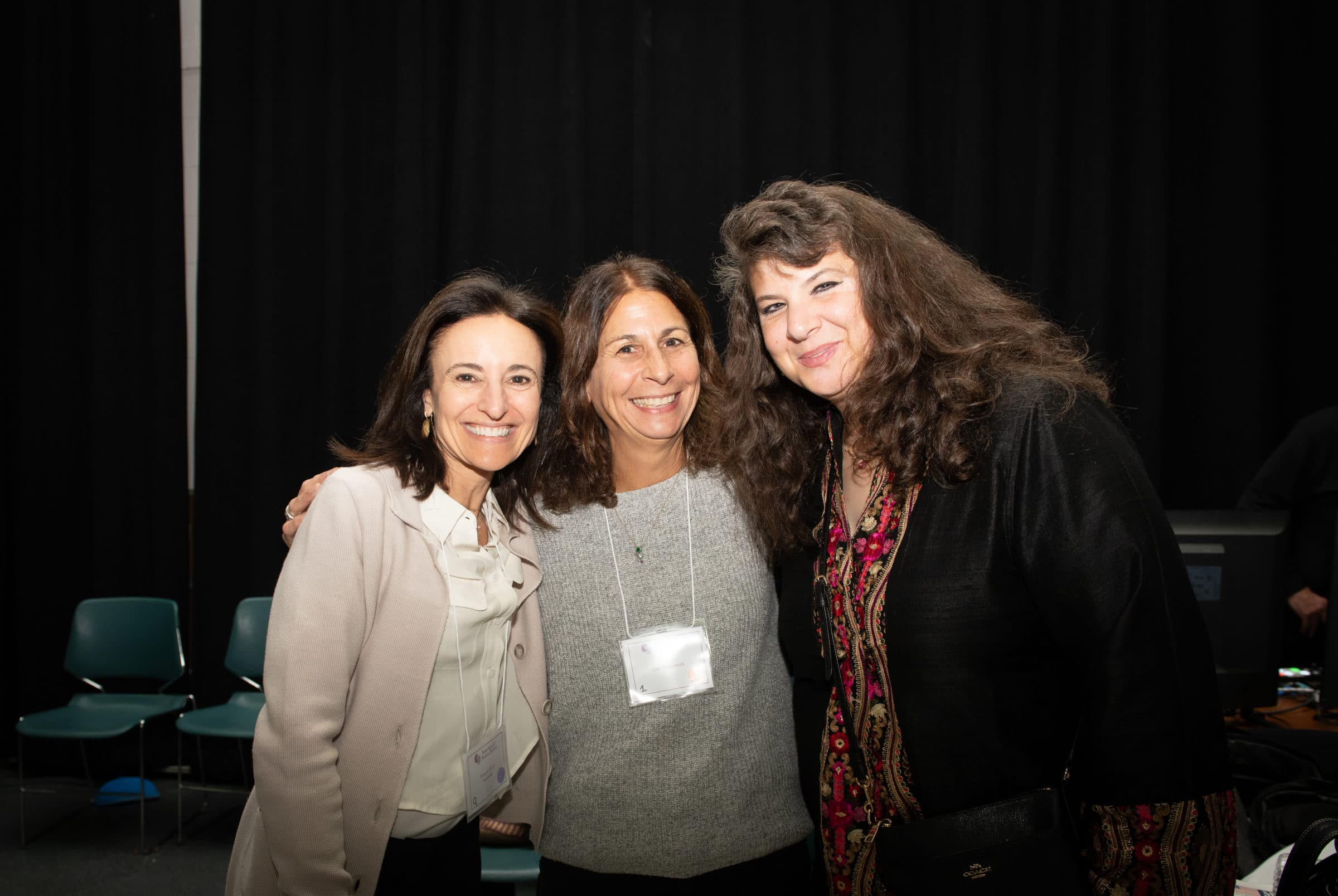 three women smiling for camera with arms around each other