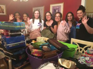 Muslim and Jewish teens waving in front of a pile of purses