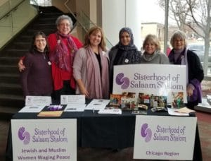 Women at table with Sisterhood banners