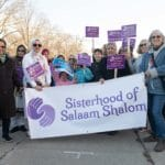 Sisters gathered with banner walking down street