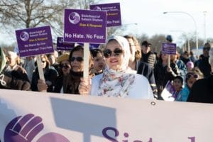 Woman in patterned hijab holding Sisterhood poster