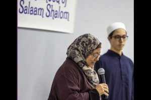 Woman in hijab holding microphone next to Sisterhood sign