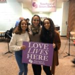 Woman in hijab with two daughters holding sign that says Love lives here.