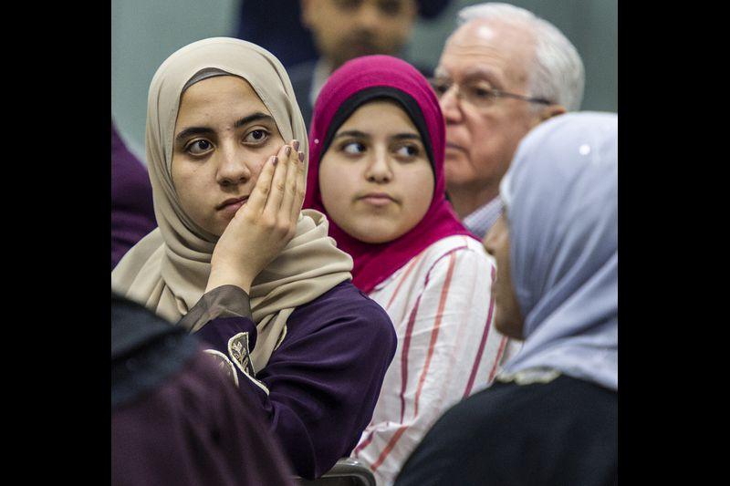 Women in hijab listening to a speaker