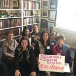 Sisters gathered with Sisterhood sign in front of bookshelves