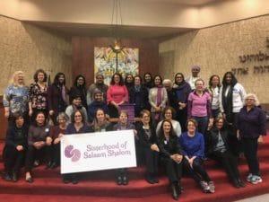 Women gathered behind Sisterhood banner