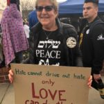 Woman in black t-shirt holding sign that says Words cannot drive out hate, only Love can do that