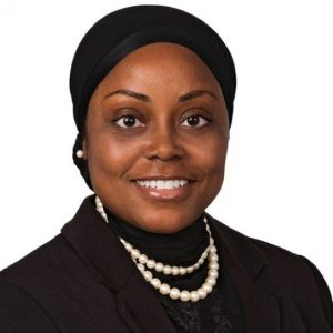 photo of black woman in headscarf with double strand pearl necklace and black blouse
