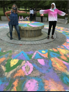 Two women in masks with hands stretched across a foundation decorated with a brightly colored chalk mandala