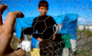 Photo of a boy with his hands in his pockets as seen through a wire fence