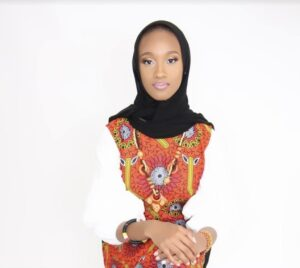 Black woman in black hijab and white, red, and yellow blouse, her hands crossed in her lap