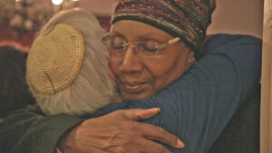 gray haired woman in kipper and African American woman in headscarf embrace
