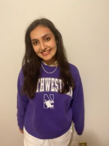 Dark haired young woman wearing a purple and white Northwestern sweatshirt