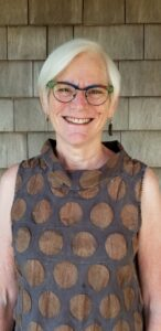 smiling woman in blue and green glasses with short white-gray hair and a sleeveless, brown with brown polka dotted top standing in front of cedar shake siding